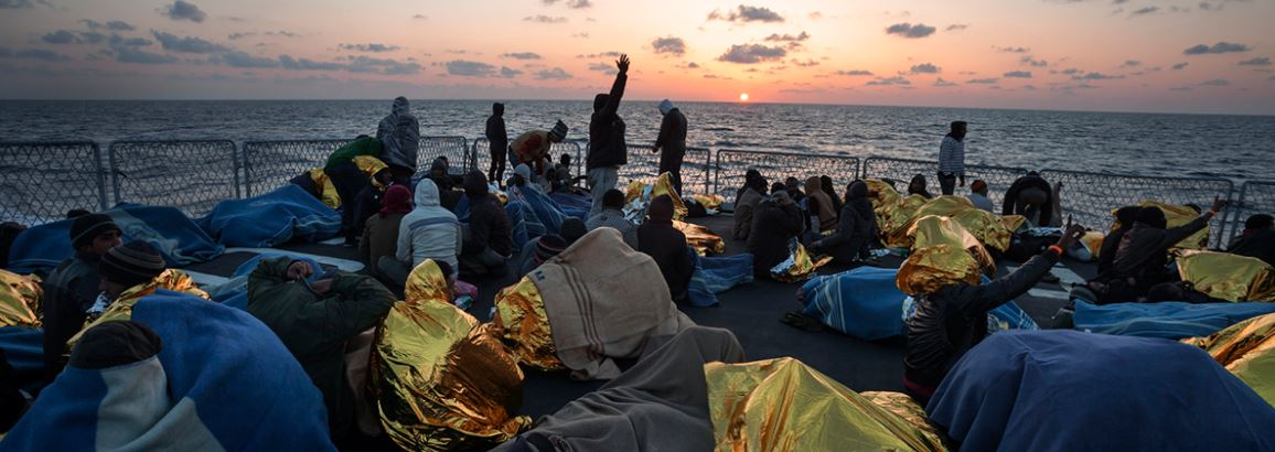 A group of rescued people on the deck of an Italian naval vessel as the sun sets in the Mediterranean. Copyright UNHCR-A. D'Amato